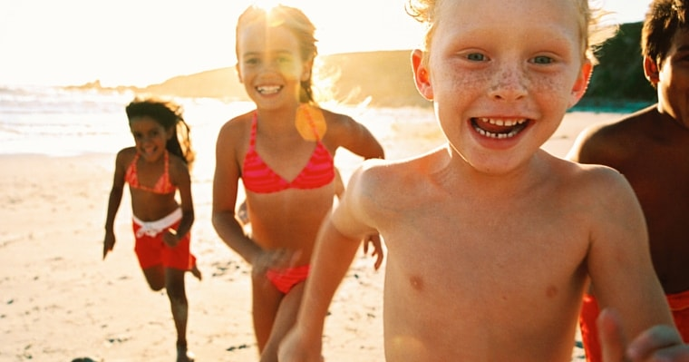 Happy, healthy children running on the beach in the sunshine, combating childhood obesity.