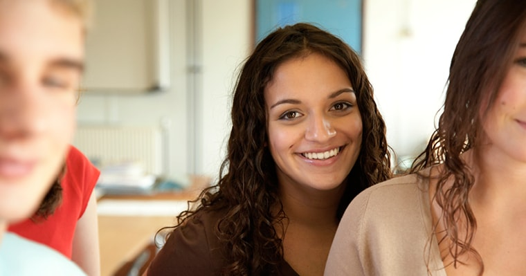 Smiling and confident young woman with perfect smile who used Invisalign Teen