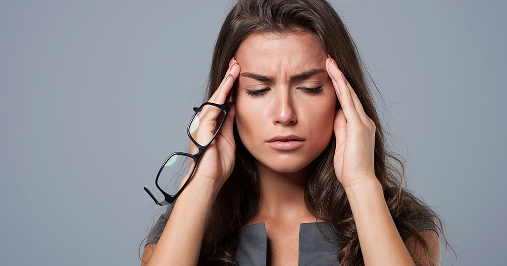 A woman holding her temples due to frequent headaches. Your dentist may be able to help you find relief with TMD treatment.